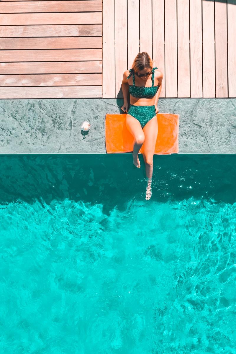 woman lying beside swimming pool during daytime